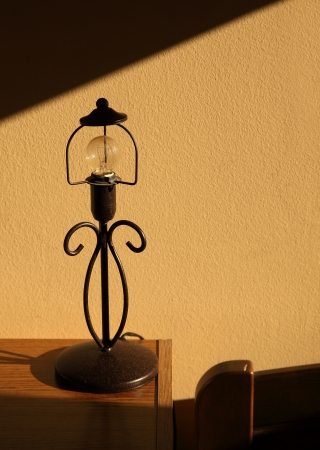 'bedside table': Wrought iron table lamp on bedside table