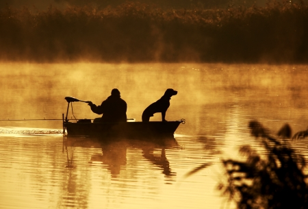 fisherman on boat: Silhouette of fisher and dog sitting in boat