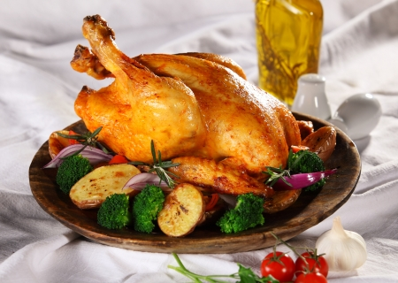 야채와 함께 접시에 구운 전체 치킨