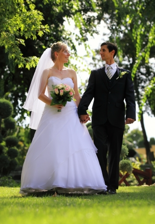 Young wedding couple walking happily outdoor photo
