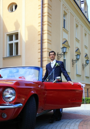 Groom standing at cabrio car photo