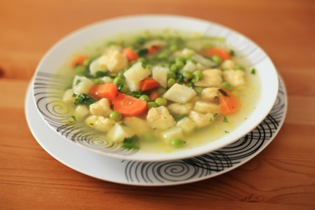 Fresh vegetable soup on wooden table photo