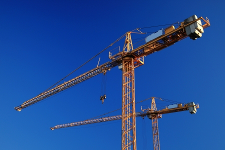 Two tower cranes against blue sky photo