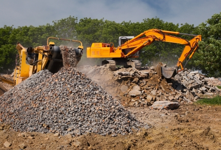 site preparation: Stone crusher and crane in working Stock Photo