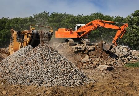 Stone crusher and crane in working Foto de archivo
