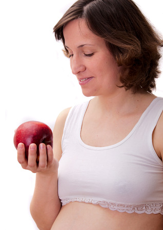 tammy: Pregnant woman holding apple in hand Stock Photo