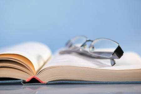 encyclopedia: Open book on blue with eyeglasses Stock Photo
