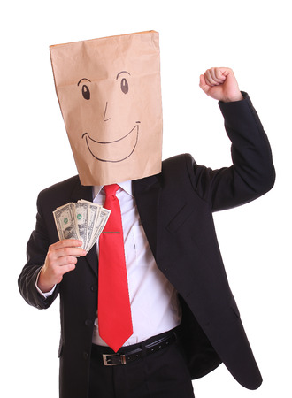 Happy businessman with a paper bag with smile on head holds money in his hand photo