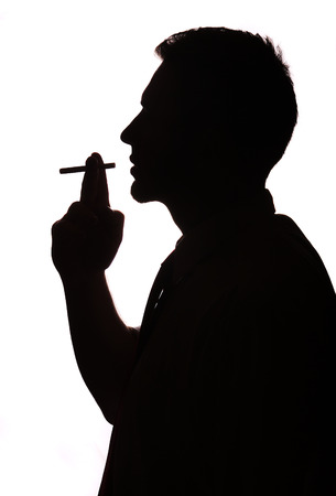 Man portrait smoking cigarette silhouette in studio isolated white background photo