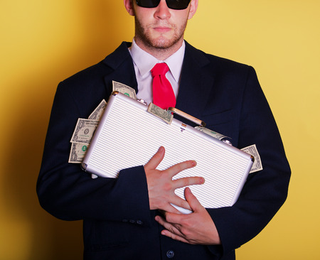 Business man with metal suitcase full of money photo