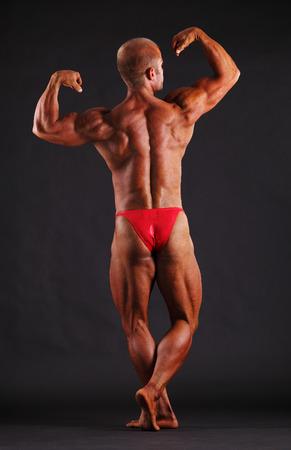 lats: Muscular male bodybuilder posing in studi