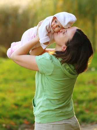 adore: Young woman lifting up her lovely baby