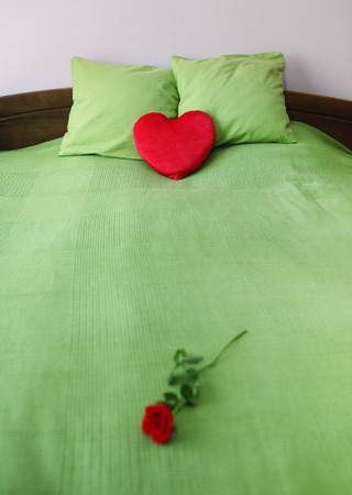 Double bed with heart shape pillow and red rose photo