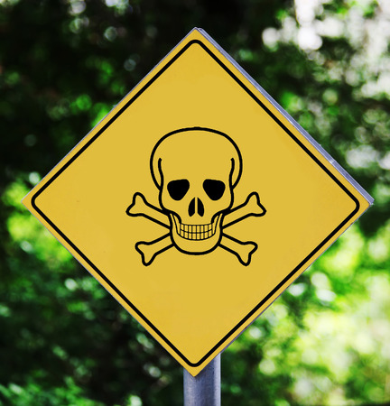 terribly: Yellow road sign outdoor with skull and crossbones pictogram