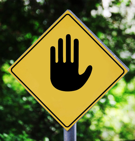 Yellow road signoutdoor with stopping hand pictogram photo
