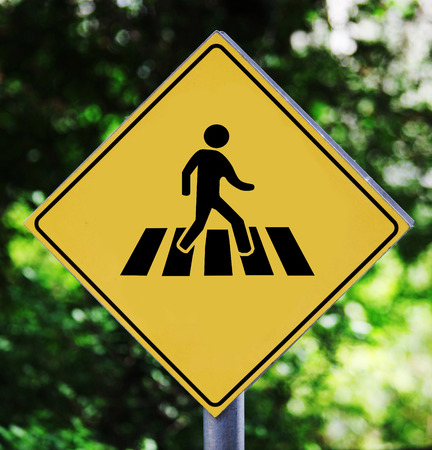 Yellow traffic label with street crossing pictogram photo