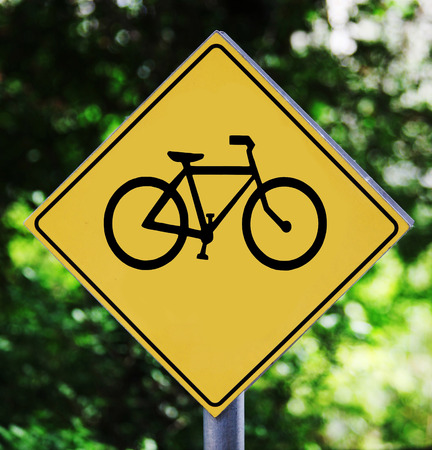 Yellow traffic label with bicycle pictogram photo