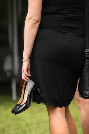 pencil skirt: Elegant woman in black dress holds leather high-heeled shoes