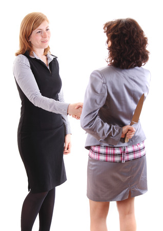 Two women make handshake on of them holds knife behind her back photo