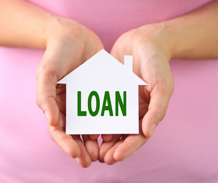 Hands of woman holding paper house with loan text photo