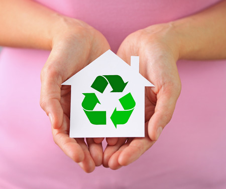 Hands of woman holding paper house with recycling symbol photo