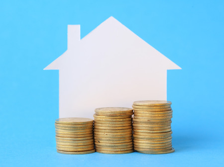 Mini house with money on blue