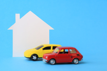 Mini house and miniature car on blue background