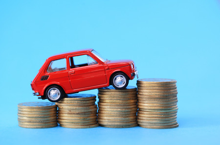 car loans: Red miniature car on coin stack Stock Photo