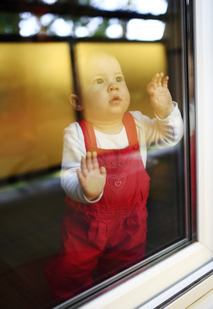 Young cute child sitting at window