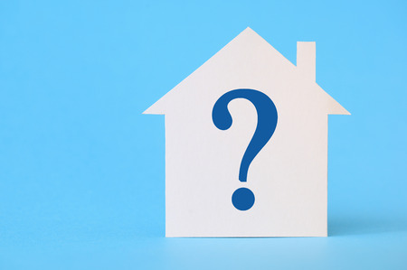 disputed: Paper house with question mark on blue background Stock Photo