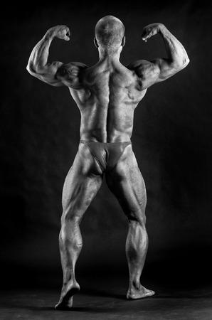 bonhomme blanc: Musculaires masculins biceps bodybuilder de flexion sur fond noir Banque d'images