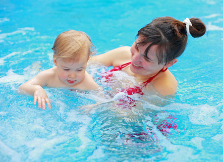 bikini pool: Lovely mother with her child in swimmingpool
