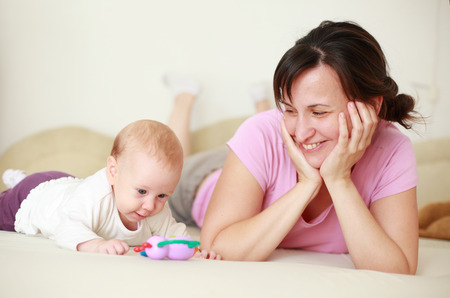 Mother adore her cute baby on bed Stock Photo