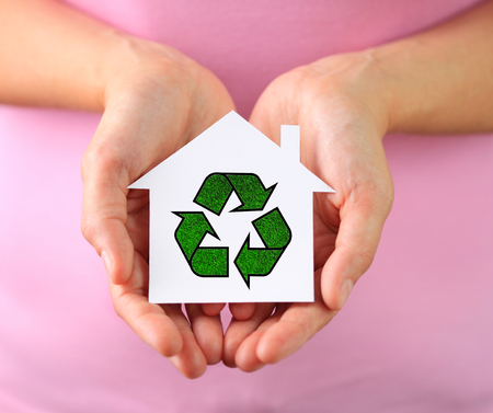hands holding house: Hands of woman holding paper house with recycling symbol
