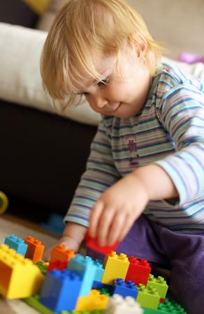 Child playing Lego bricks on floor