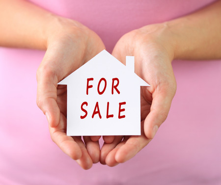 sold small: Hands of woman holding paper house