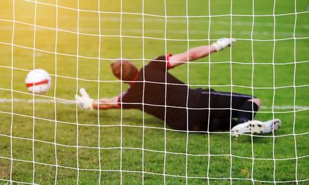 losing control: Soccer football goalkeeper making diving save