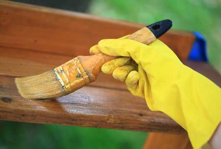 lacquerware: Gloved hand varnishing outdoor plank