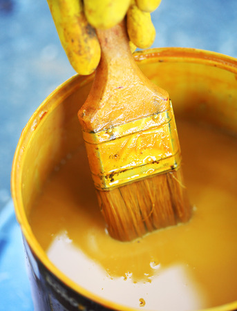 yellow paint: Bucket with yellow paint with paintbrush Stock Photo