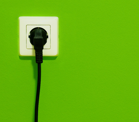 Cable connector plug in on green wall