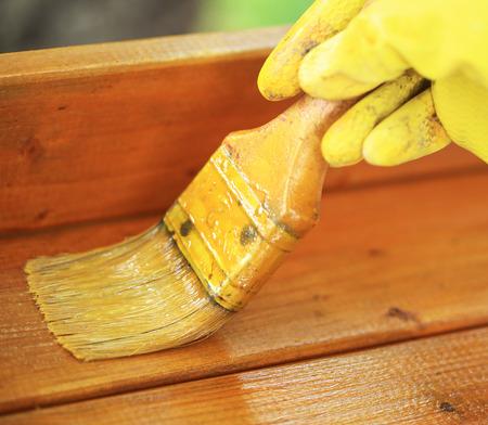 gloved: Gloved hand varnishing outdoor plank