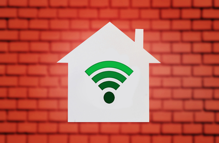 House shape on red brick wall with wi-fi sign