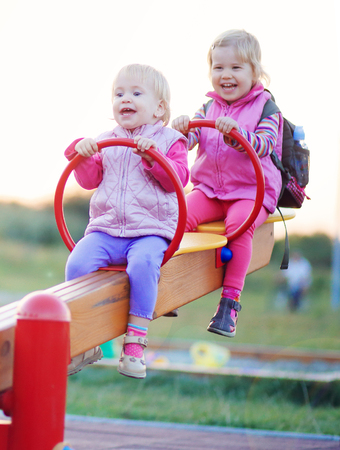 Two children play teeter-totter outdoor