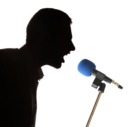 bawl: Silhouette man portrait profile screaming angry in microphone