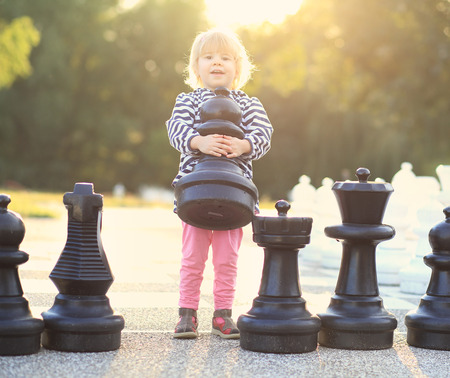 Child with huge outdoor chess figures