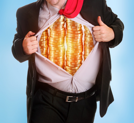 Businessman tearing his shirt coins piles it on