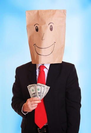 Happy businessman with a paper bag on head with smile holds money in his hand
