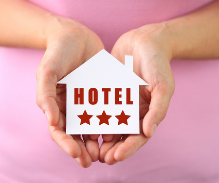 Hands of woman holding paper house hotel with text