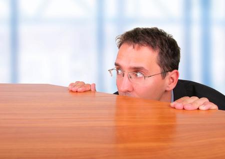 Business man hide behind table