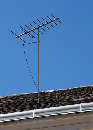 Television antenna on the roof over blue sky Stok Fotoğraf